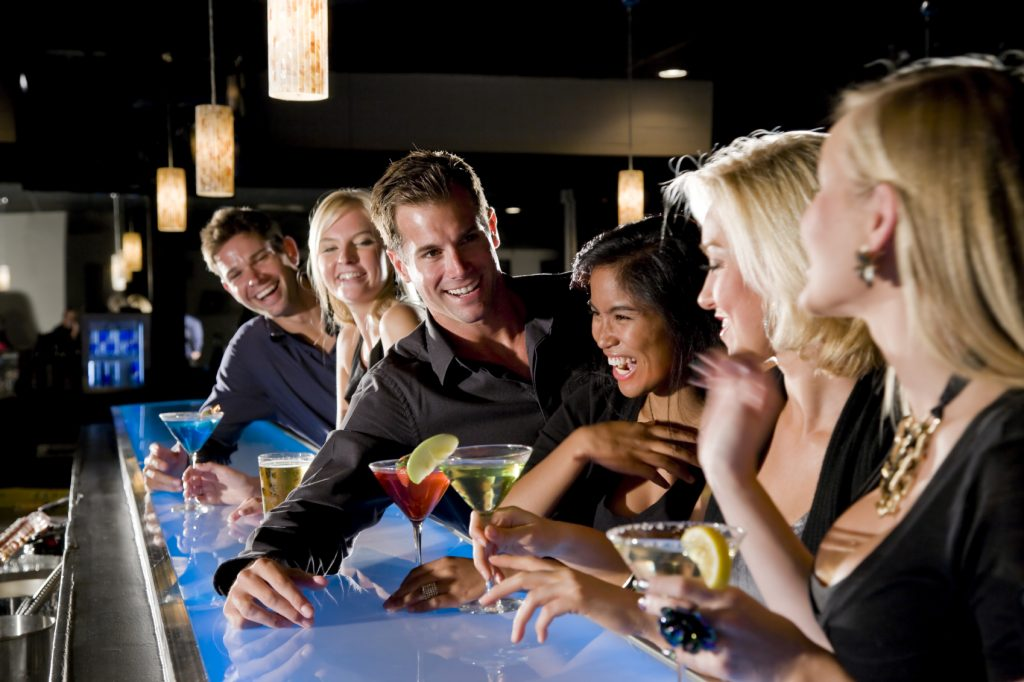 Group of people with drinks at nightclub bar